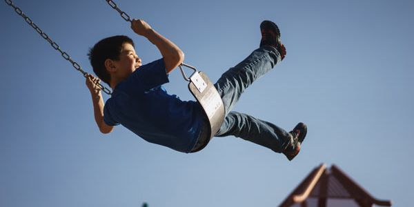 A boy on a swing against a background of blue sky and playground equipment