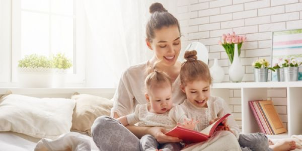 Woman reads to baby and girl on bed