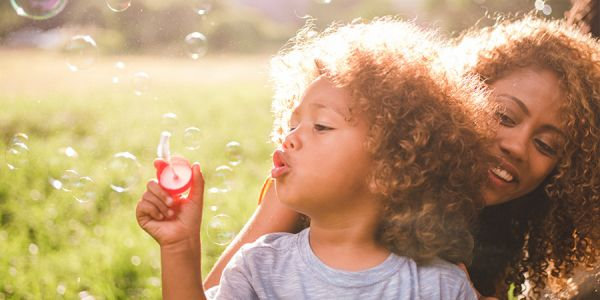 Woman and child blow bubbles in sunny field