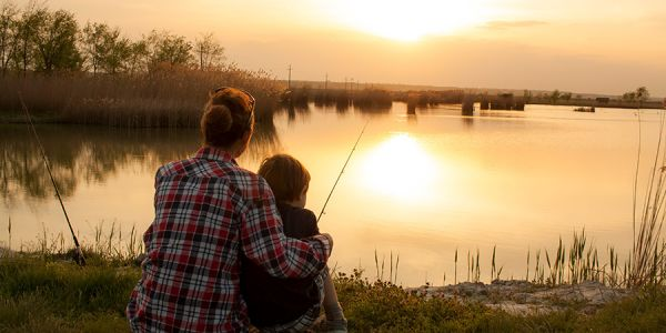 Woman holds boy while fishing from shore at sunset