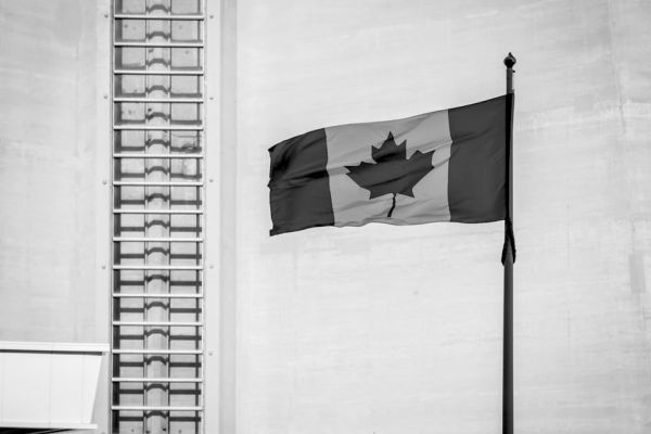 Greyscale Canadian flag against stark concrete building