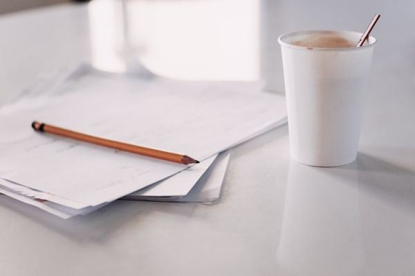 Pencil, papers, and coffee cup sit on a white surface