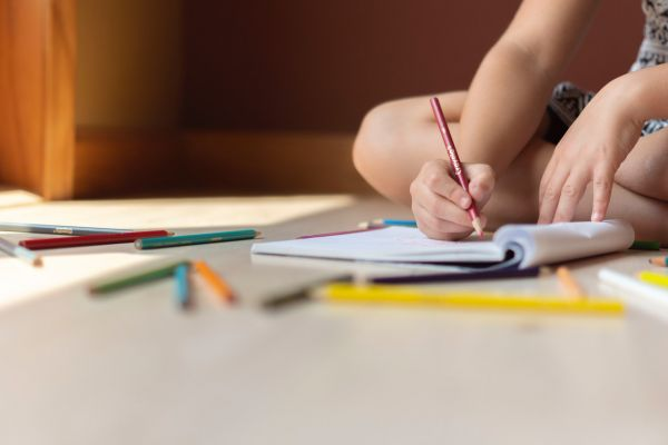 Closeup of a child drawing in a notebook with coloured pencils on the floor
