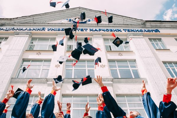 Hands throwing up mortarboards in front of white building