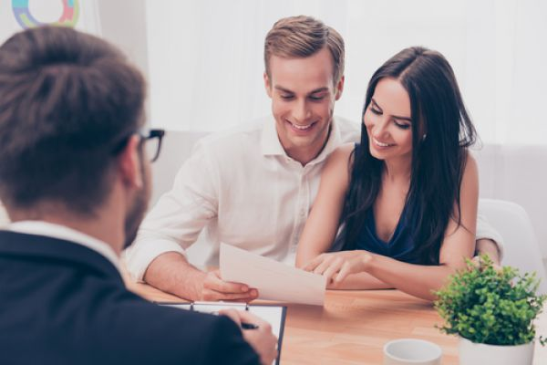 Couple looks excitedly at documents across the table from a man with a clipboard