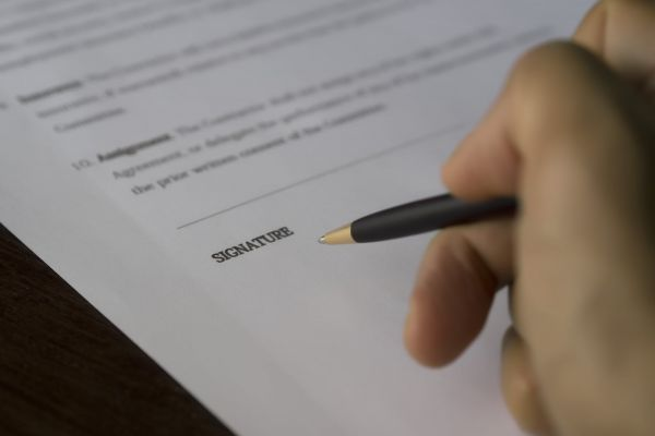 A hand is ready to apply a signature with a pen to a document