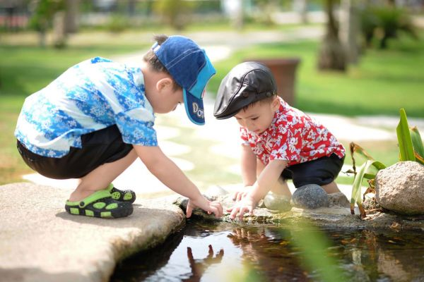 Two young boys play by a pond beside a concrete path in a park