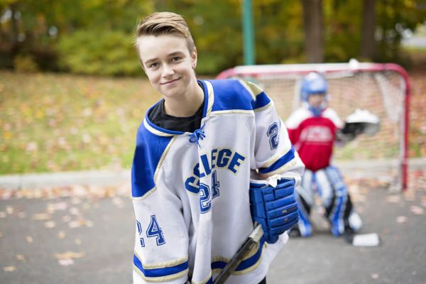 Two boys pose with road hockey gear in Autumn