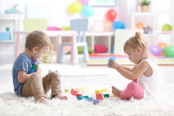 Boy and girl play on thick white shag carpet in playroom
