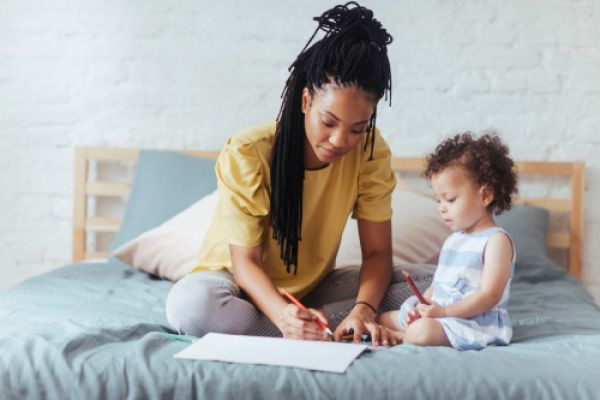 Woman and toddler sitting on a large bed colouring with pencils and paper
