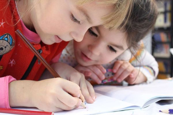 A young girl writes in a notebook while her friend watches closely