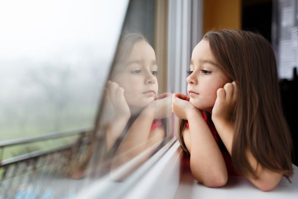 Young girl rests on her elbows while looking out a window