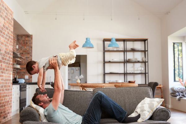 Man holds young boy up in the air while lying on living room couch
