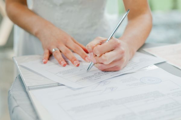 Womans hand signing documents