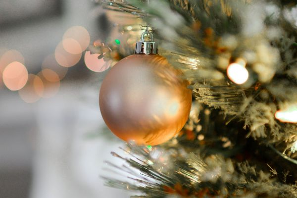 Single gold Christmas bulb on tree branch