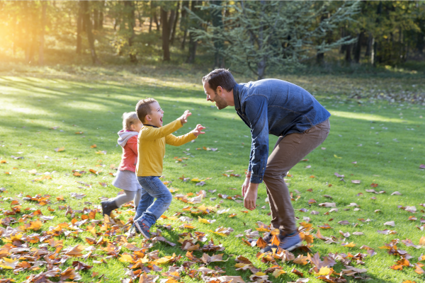 Two children run through fallen leaves toward crouching man