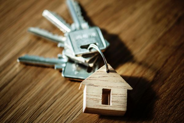 Set of keys on wooden surface with house-shaped key fob