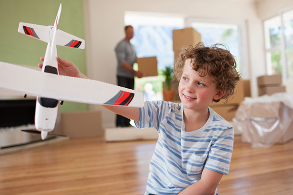 Boy plays with airplane while man in background deals with moving boxes