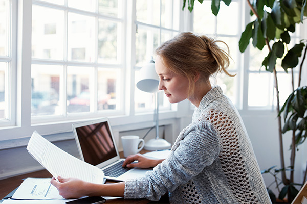Woman looks at papers in well-lit window desk